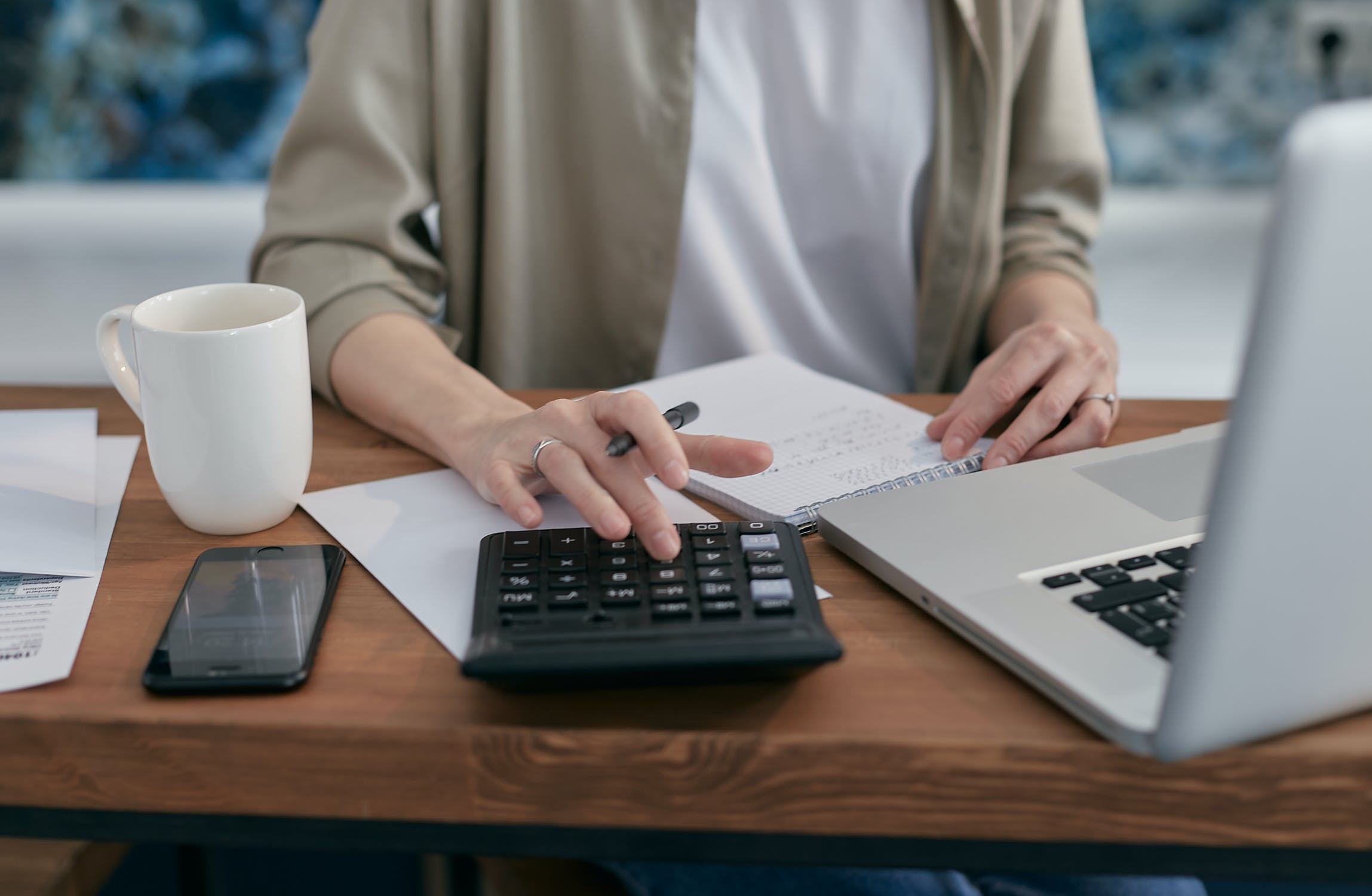 woman with calculator and computer - PHP Invoice